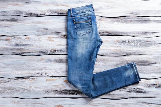 Effen blauwe spijkerbroek. casual jeans op houten achtergrond. regular fit broek op showcase. gloednieuw denim kledingstuk.