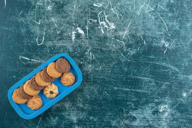 Effen en chocoladekoekjes op een houten dienblad, op het blauwe oppervlak