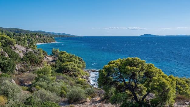 Egeïsche kust van griekenland, rotsachtige heuvels met groeiende bomen en struiken, uitgestrekt water
