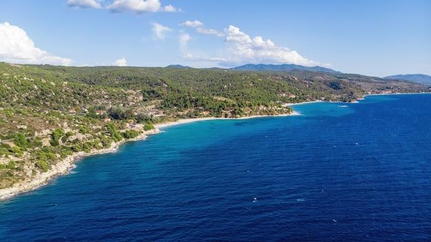 Egeïsche kust van griekenland, rotsachtige heuvels met groeiende bomen en struiken, weinig gebouwen aan de kust, uitgestrekte water