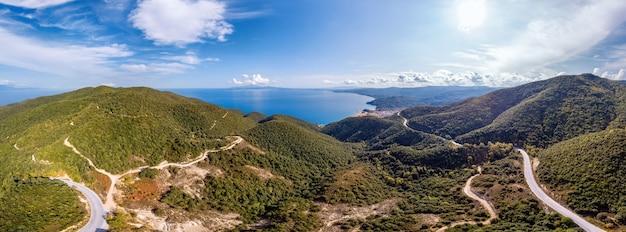 Egeïsche zee kosten van griekenland, kronkelende weg, heuvels bedekt met weelderig groen, uitzicht vanaf de drone