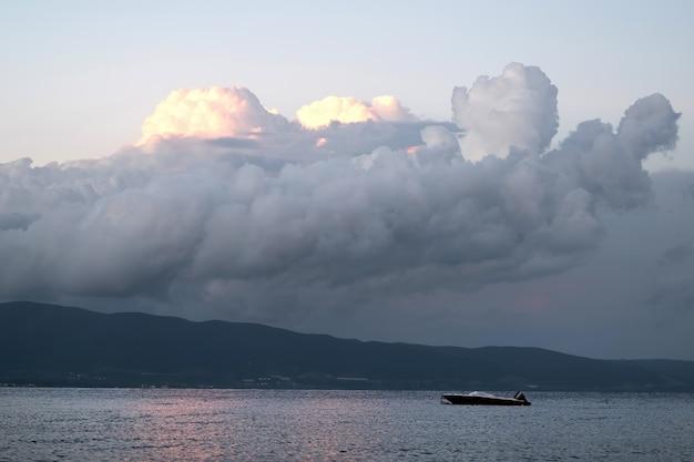 Egeïsche zee met een boot, weelderige wolken verlicht door onder te gaan, griekenland