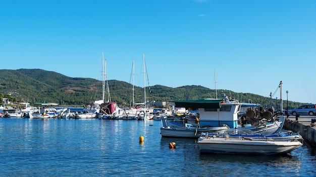 Egeïsche zeehaven met meerdere afgemeerde jachten en boten, helder weer in neos marmaras, griekenland