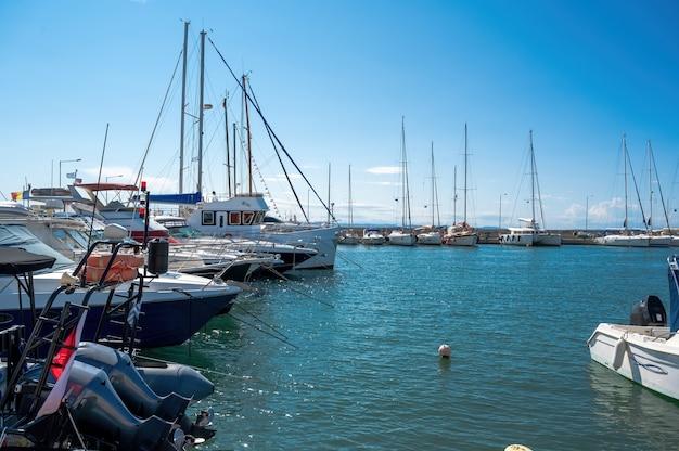 Egeïsche zeehaven met meerdere afgemeerde jachten en boten, helder weer in nikiti, griekenland