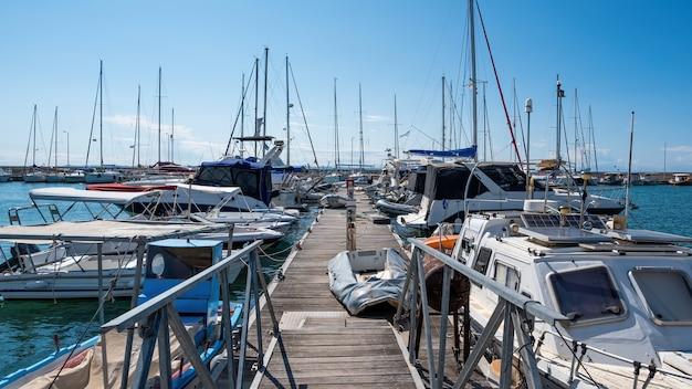 Egeïsche zeehaven met meerdere afgemeerde jachten en boten, houten pier, helder weer in nikiti, griekenland