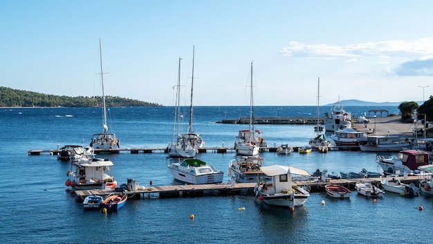 Egeïsche zeehaven met meerdere afgemeerde jachten en boten, houten pieren, helder weer in neos marmaras, griekenland