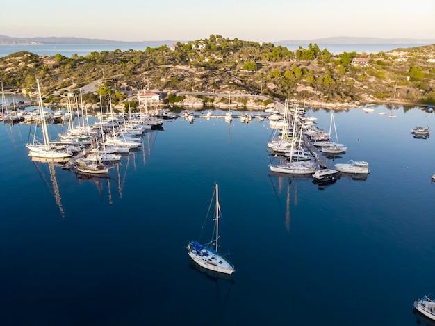 Egeïsche zeehaven met meerdere afgemeerde jachten in de buurt van pieren, groen, blauw water, uitzicht vanaf de drone, griekenland