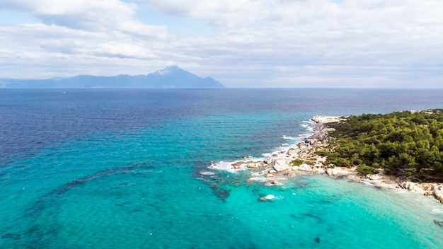 Egeïsche zeekust met blauw transparant water, groen rond, rotsen, struiken en bomen, uitzicht vanaf de drone, griekenland