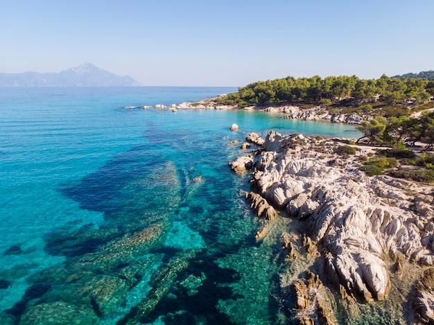 Egeïsche zeekust met blauw transparant water, groen rondom, rotsen, struiken en bomen, uitzicht vanaf de drone, berg griekenland