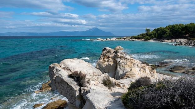 Egeïsche zeekust met groen rondom, rotsen, struiken en bomen, blauw water met golven, bergen