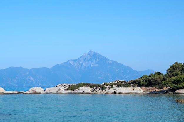 Egeïsche zeekust met rotsen en rustende mensen, berg in de verte, groen op de voorgrond, blauw water, griekenland