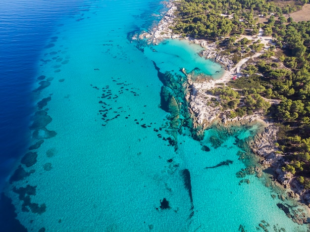 Egeïsche zeekust met rotsen in de buurt van de kust en onder het blauwe transparante water, groen, uitzicht vanaf de drone, griekenland