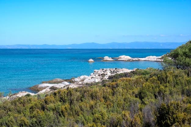 Egeïsche zeekust met rotsen over het water en land in de verte, groen op de voorgrond, blauw water, griekenland