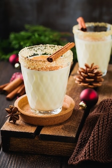 Eggnog traditionele kerstdrank milkshake met kaneel op donkere oude achtergrond.