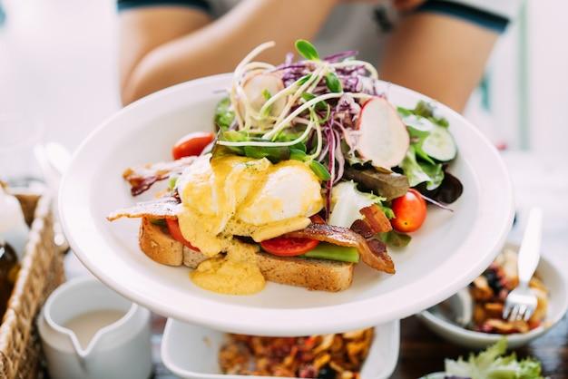 Eggs benedict geserveerd met toast krokant spek asperges gesneden tomaat en rucola mix met gesneden paarse kool, komkommer en radijs.