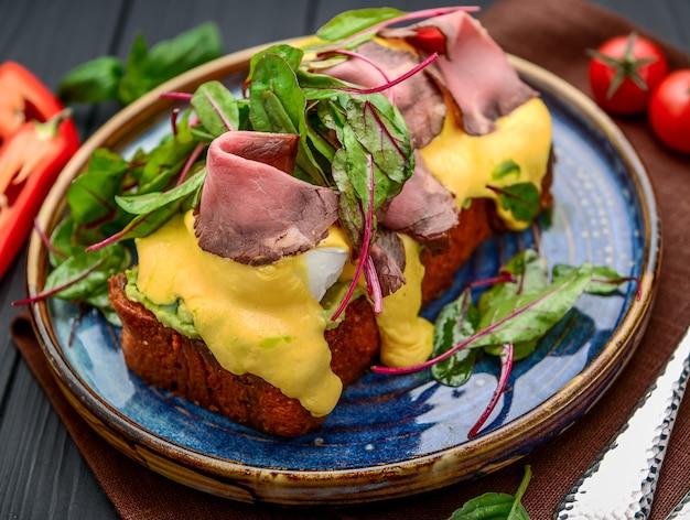 Eggs benedict op toast met ham en saus. ontbijt in het restaurant