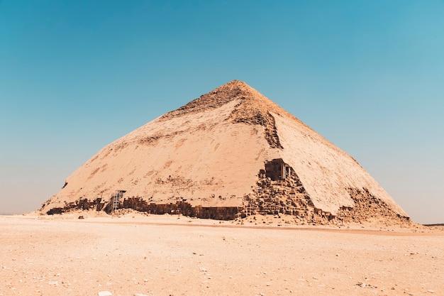 Egypte. dahshur of dashur. de gebogen piramide stond ook bekend als valse of ruitvormige piramide vanwege de veranderde hoekhelling van farao sneferu met goed bewaard gebleven originele kalkstenen behuizing
