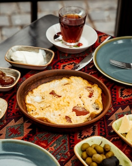 Ei en worst schotel in aardewerk pan geserveerd voor het ontbijt