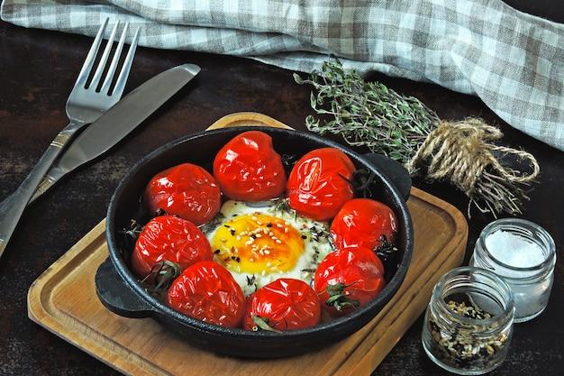Ei gebakken met cherrytomaatjes en tijm in een gietijzeren koekenpan. gezond ontbijt. keto ontbijt.