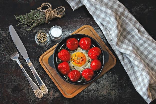 Ei gebakken met cherrytomaatjes en tijm in een gietijzeren koekenpan.