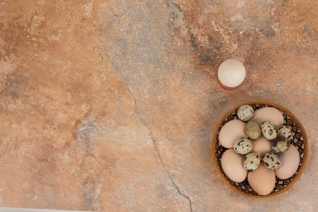Ei in de beker en verschillende witte eieren op de mand.
