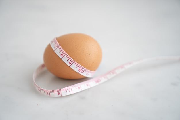 Ei omwikkeld met meetlint op wit marmeren oppervlak