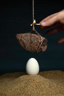 Ei onder een steen die aan een touw hangt
