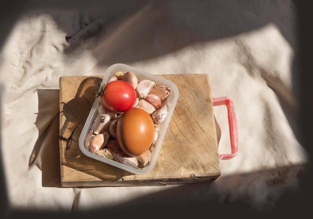 Ei, tomaten en knoflook in containers met selectieve aandacht shoo