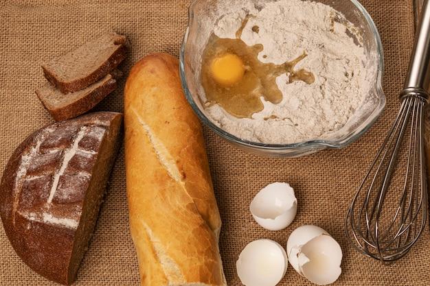 Eierdooier op de bloem. eierschalen, stokbrood en roggebroodjes en handmixer op een stuk jute. bovenaanzicht