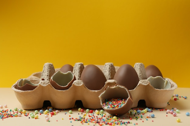 Eierdoos met chocolade-eieren met hagelslag op beige tafel