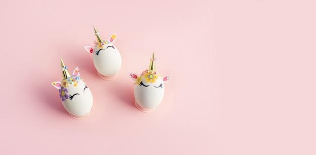 Eieren beschilderd met eenhoorn-thema op roze oppervlak. pasen concept