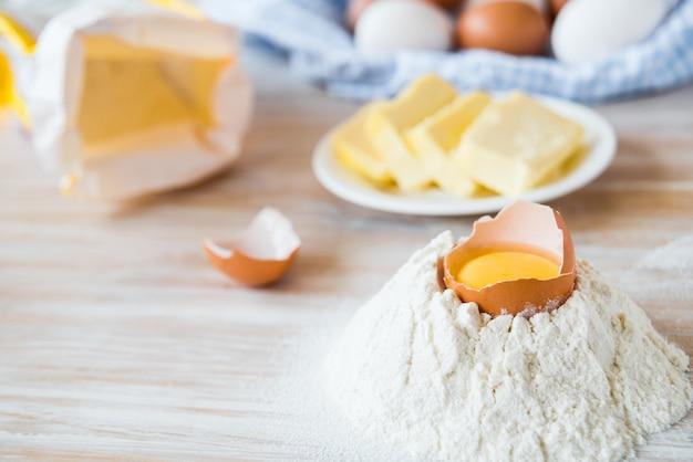 Eieren, bloem, boter, pasta of bakselingrediënten op een houten tafel. selectieve aandacht