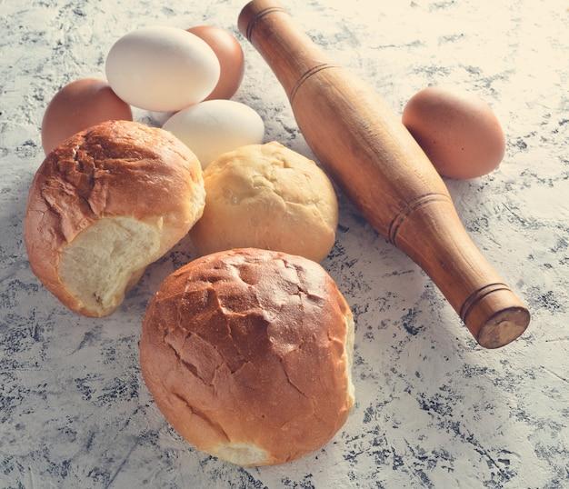Eieren, deegroller, broodjes op een witte betonnen tafel