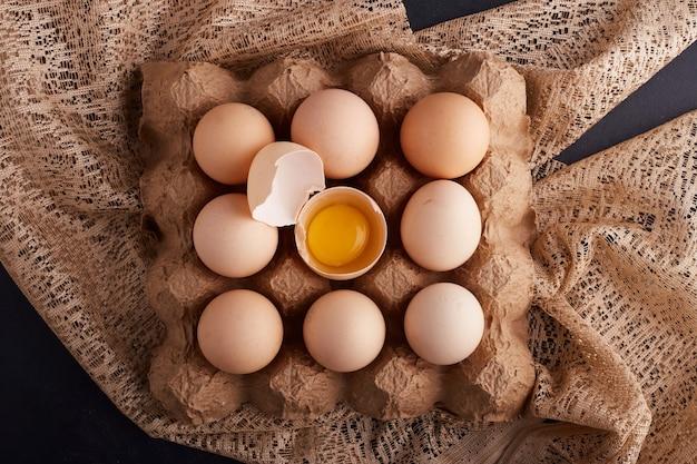 Eieren en dooier in eierschaal in de kartonnen bak op een stuk jute, bovenaanzicht.