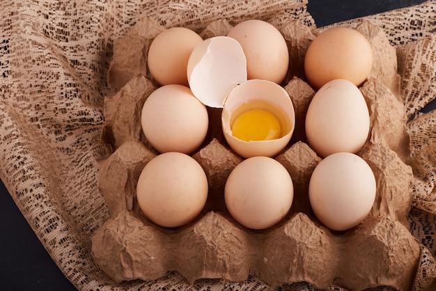 Eieren en dooier in eierschaal in de kartonnen bak op een stuk jute.