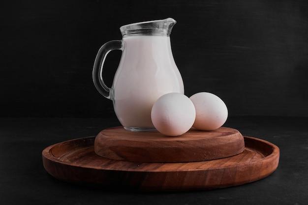Eieren en een potje melk op een houten bord.
