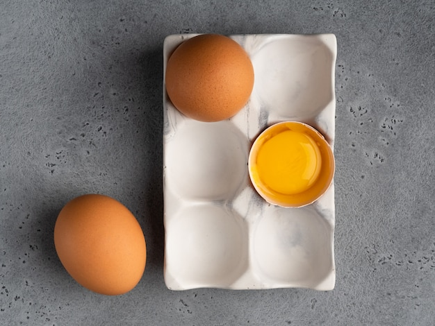 Eieren en eierdooier, eischaaltje in witte ceramische houder op grijze concrete achtergrond. bovenaanzicht