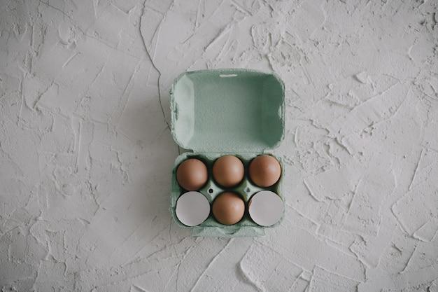 Eieren en eierschalen in een doos op tafel