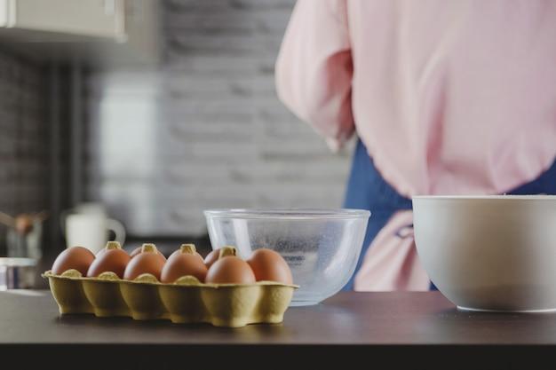 Eieren en kommen inpakken voor het maken van deeg op de achtergrond van de keuken en de vrouw die thuis kookt