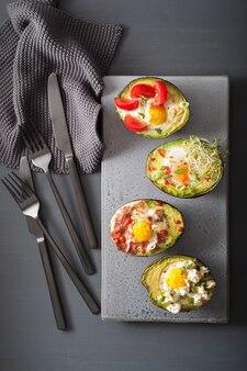Eieren gebakken in avocado met spek, kaas, tomaat en alfalfaspruiten