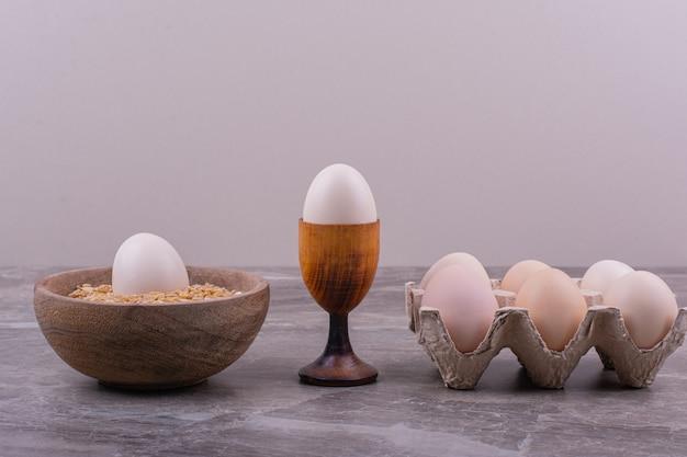 Eieren geïsoleerd in een houten beker op de steen
