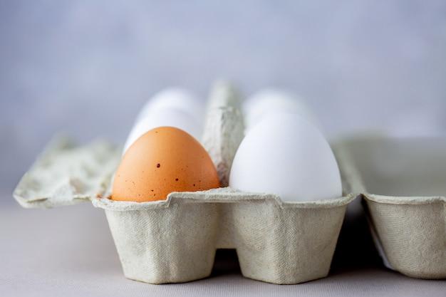 Eieren in een doos met verschillende kleuren. eiwit. gezond eten. gezond eten. eieren als ontbijt. eieren in de koelkast op de plank. doos met eieren op een grijze achtergrond