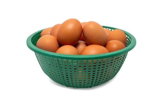 Eieren in een groene mand op wit wordt geïsoleerd