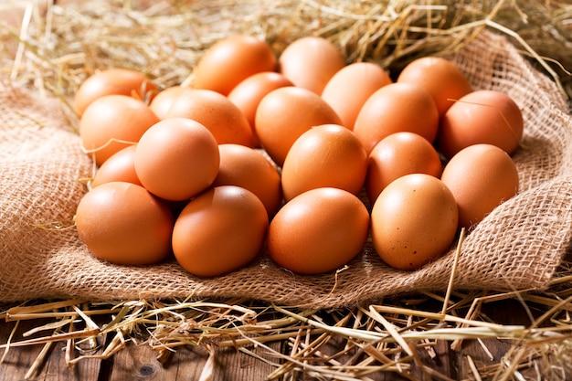 Eieren in een hoop hooi op houten tafel