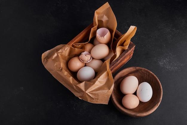 Eieren in een houten beker en op het rustieke papier.