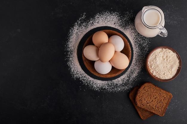 Eieren in een houten beker met een pot melk opzij, bovenaanzicht.