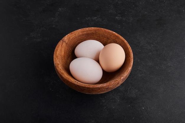 Eieren in een houten kop op zwarte ruimte.