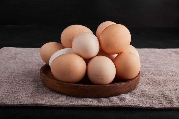 Eieren in een houten schotel op keukenhanddoek.