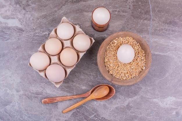 Eieren in een kartonnen bakje en in een houten beker