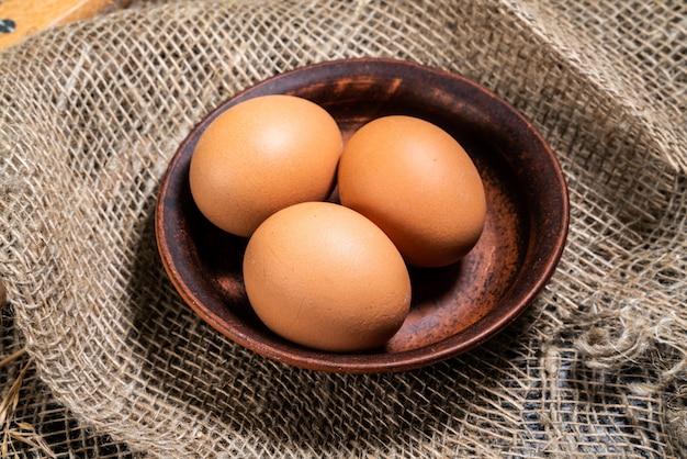 Eieren in een kleikom op een natuurlijke stof. het concept van het maken van brood, thuis bakken